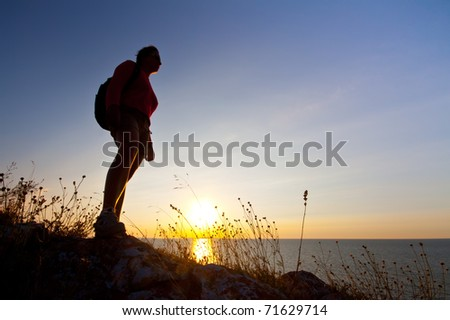 Silhouette of hiking woman near sea