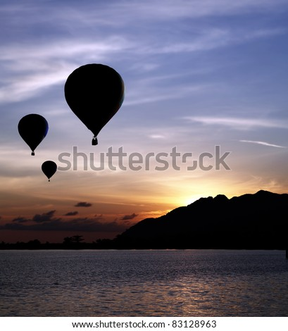 Silhouette of hot air balloons floating up to the sky during a fiery surreal sunset against a mountain at a rural remote seaside.