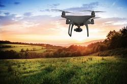Silhouette of hovering drone taking pictures of nature at sunset