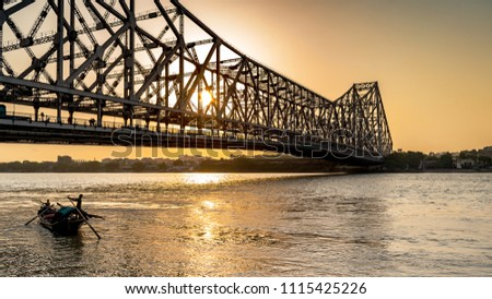 Silhouette of Howrah Bridge at the time of Sunrise.  Howrah Bridge is a bridge with a suspended span over the Hooghly River in West Bengal. #1115425226