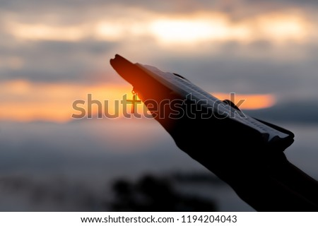 Silhouette of human hand holding bible and cross, the background is the sunrise., Concept for Christian, Christianity, Catholic religion, divine, heavenly, celestial or god. #1194204043