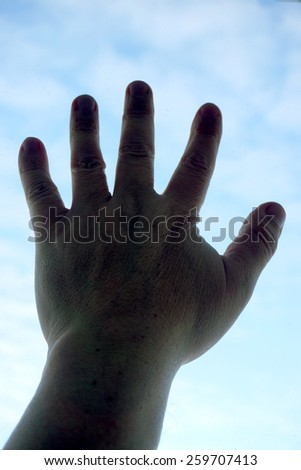 Silhouette of human hand on sky background