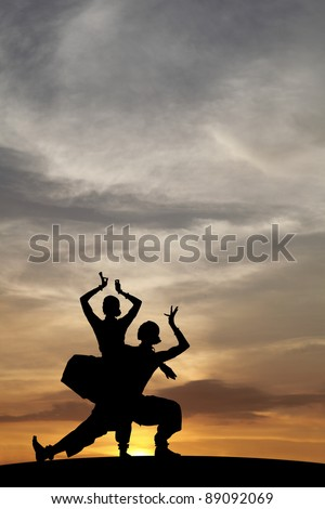 Silhouette of Indian cultural classical dancer posing on a hill against a surreal dramatic sunset sky.