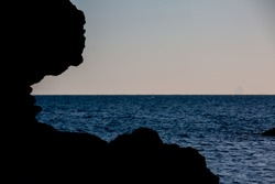 Silhouette of isolated cliff on sea coast with deep blue sea on sunset
