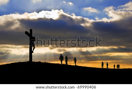 Silhouette of Jesus Christ crucifixion on cross on Good Friday Easter with people walking up hill towards Jesus