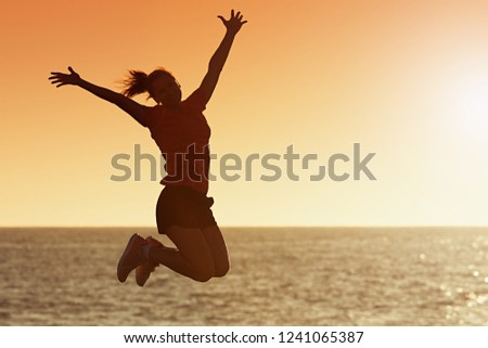 Silhouette of joyful woman jumping and having fun at the beach against the sunset, freedom and leisure vacation concept #1241065387