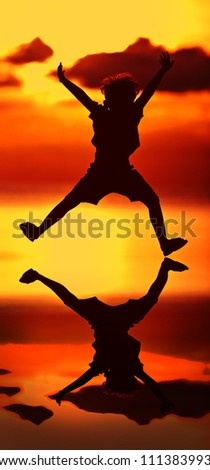 silhouette of  jumping happy boy at dusk.