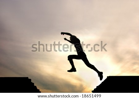 silhouette of jumping man against sunset