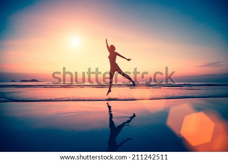 Silhouette of jumping woman on the beach at sunset.