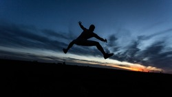 Silhouette of jumping young man on beautiful sunset sky. Design element. Business concept.
