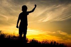Silhouette of kid and the beautiful sky in the evening