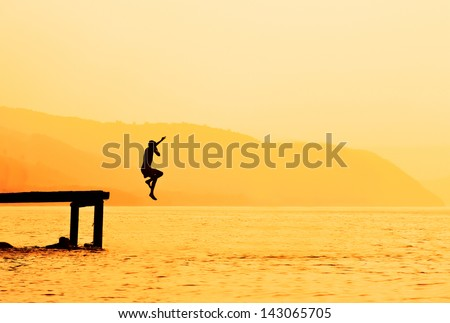 Silhouette of kids jumping from river dock, at sunset.