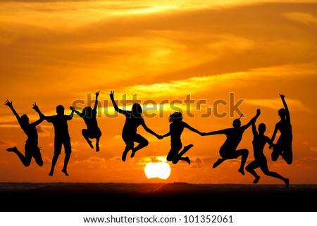 silhouette of kids jumping on beach in sunset - stock photo