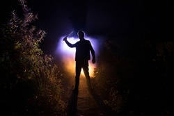 Silhouette of killer with knife standing in the dark forest with light. Horror halloween concept. strange silhouette in a dark spooky forest at night