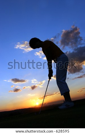 Silhouette of lady golfer just before sunset