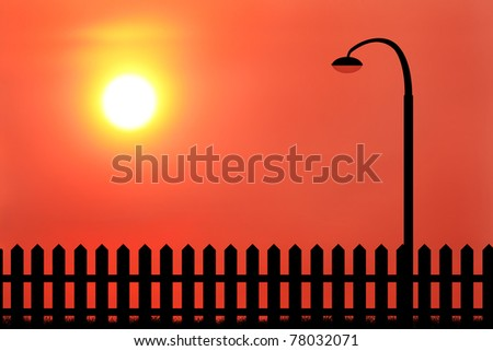 silhouette of lamppost and wood fence during sunset
