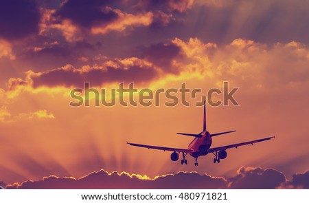 Silhouette of landing airplane at dawn - Shutterstock ID 480971821