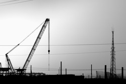 Silhouette of lattice boom crawler crane at construction site in oilfield at sunset - black and white