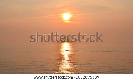 Silhouette of local small fishing boat moving on the calm sea with sunrise in the background. #1032896389