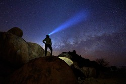 Silhouette of lone woman on rounded rocky structures gazing at milky way and the stars,  focused beam of headlamp pointing directly to milky way. Night sky photo. Twyfelfontein, Damaraland, Namibia.