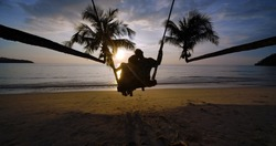Silhouette of lovely couple on the beach. Young hipster man and woman sitting together on rope swing hugging and kissing while enjoying their summer holidays vacation together on a seaside at sunset.