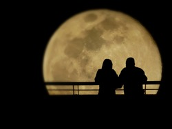 Silhouette of lovers watching full moon in the romantic night