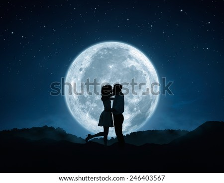Silhouette of loving couple kissing against the full moon