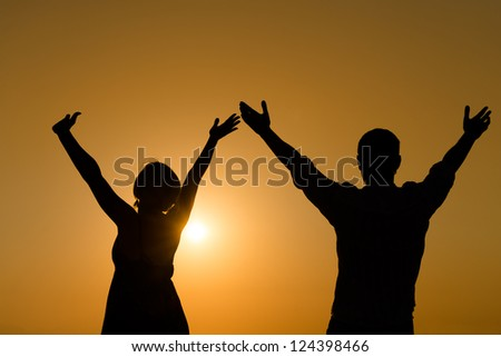 Silhouette of loving couple raise their hands with enjoy over orange sunset background