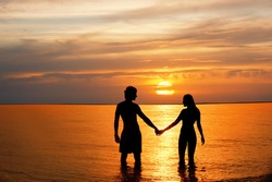 Silhouette of male and woman in sea against sunset.