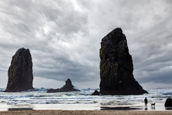 Silhouette of man and dog contemplating a dramatic sky at Canon Beach, Oregon with rocky seascape on a windy and cloudy afternoon.