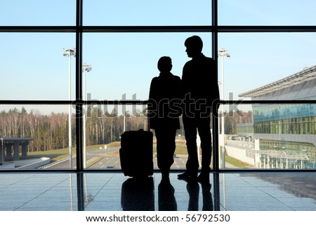 silhouette of man and girl with luggage standing near window in airport