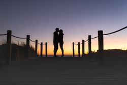 Silhouette of man and woman couple kissing at a beautiful sunset on the beach.