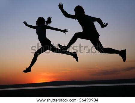 silhouette  of man and  woman run together on a sunset on lake coast