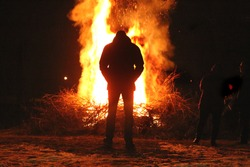 Silhouette of man by the fire at night. Man standing in front of bonfire. Flame on the ground.