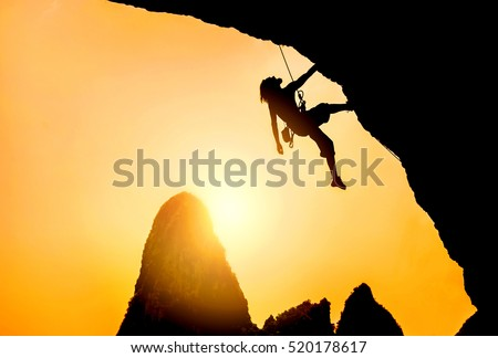 silhouette of man climbing at...