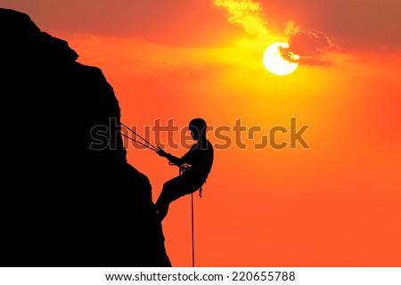 Silhouette of man climbing on rock (mountain) at sunset