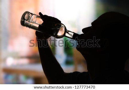 Silhouette of man drinking alcohol close up