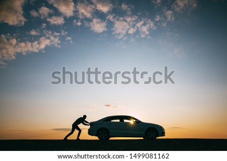 Silhouette of man driver pushing his car along on an empty road after breakdown at sunset, copy space, side view.  Stock photo ©