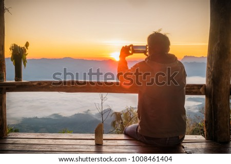 silhouette of man hands holding mobile phone at sunset above winter mountains. male makes a photo on your phone. The glare of the sun illuminate the silhouette.