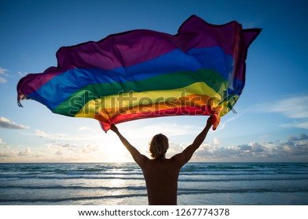 Silhouette of man holding a gay pride rainbow flag fluttering against the rising sun on an empty beach