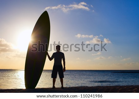 Silhouette of man holding paddle board on a beach at sunset