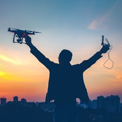 Silhouette of man holding switched on Drone quad copter and Remote control enjoying freedom, victory, success. Cityscape with dramatic sunset sky in the background. Business concept, raised hands
