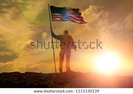 Silhouette of man holding US flag American on the mountain. The concept of Independence Day. a successful silhouette winner, a man waving an American flag on top of a mountain peak #1151530139