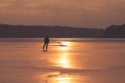 Silhouette of man ice skating on the pond, evening sun. Ice.