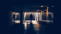 silhouette of man in a subway tunnel. Light at end of tunnel. Person walking down a dark corridor