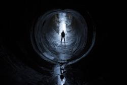 silhouette of man in circular tunnel