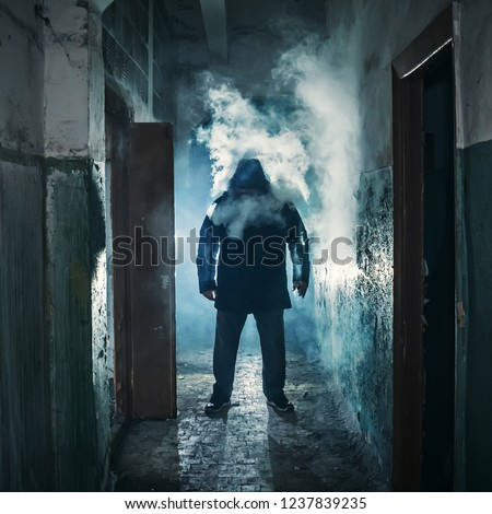 Silhouette of man in dark creepy corridor in clouds of vape steam or vapor smoke, mystery horror atmosphere, toned