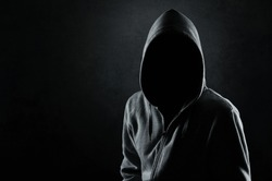 Silhouette of man in the hood or hooligan over dark concrete background with copy space