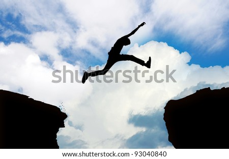 Silhouette of man jumping cliff with cloudy sky