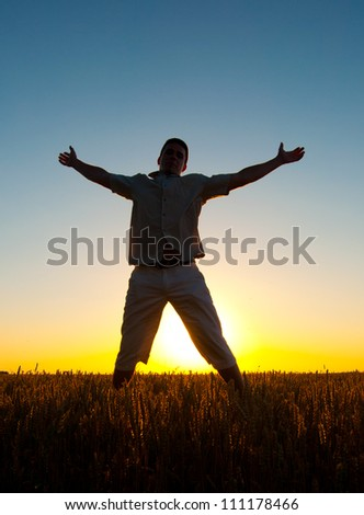 Silhouette of man jumping high in the wheat field on sunny summer day.